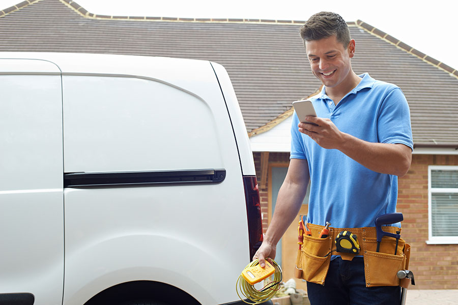 Contact - Happy Electrician Next To Van Using Phone